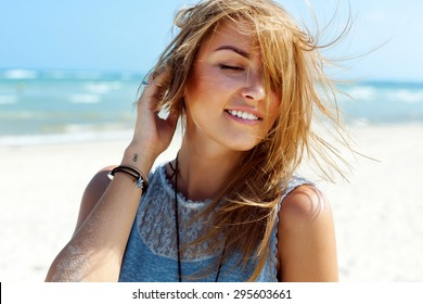 Young pretty blonde fashion girl sensual portrait posing outdoor in summer having fun on fresh air wind blowing hairs smiling
