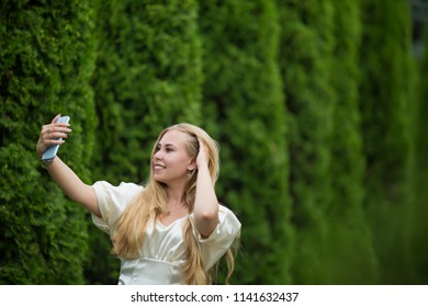 Young pretty blonde girl in a dress makes a selfie between thuja on the street in summer.