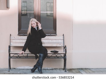 Young pretty blonde girl on the urban bench