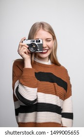 Young pretty blonde girl in striped brown sweater with lips painted bright red lipstick, long hair smiling, holding vintage photo camera, looking at viewfinder and taking picture on white background