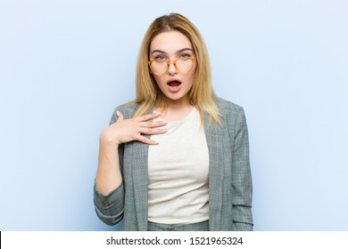 young pretty blonde woman feeling shocked, astonished and surprised, with hand on chest and open mouth, saying who, me? against flat wall