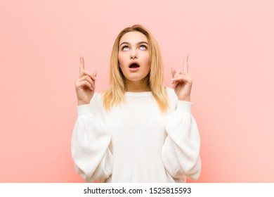 young pretty blonde woman looking shocked, amazed and open mouthed, pointing upwards with both hands to copy space against pink flat wall