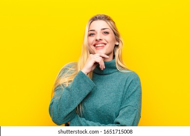 young pretty blonde woman looking happy and smiling with hand on chin, wondering or asking a question, comparing options against yellow wall