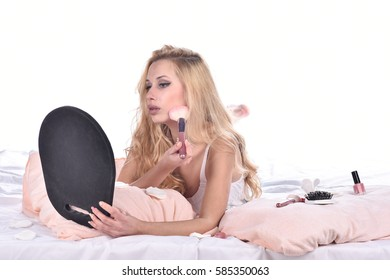Young pretty blonde woman with natural curly hair in bed isolated on white background applying makeup with brush and looking her self in mirror