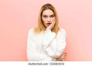 young pretty blonde woman open-mouthed in shock and disbelief, with hand on cheek and arm crossed, feeling stupefied and amazed against pink flat wall