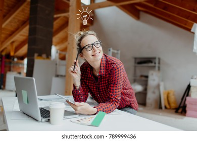 young, pretty, blonde woman is planning on the notebook and tablet the expansion of her loft and a light goes on her
