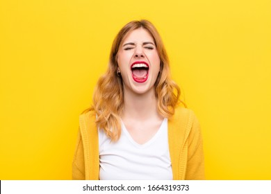 young pretty blonde woman shouting aggressively, looking very angry, frustrated, outraged or annoyed, screaming no against yellow wall