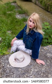 Young pretty blonde woman with vintage hat waiting on rustic bridge