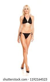 young pretty blonde woman walking in black bikini on white background