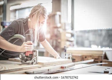 young pretty blonde woman works with the Lamello groove milling machine in the carpentry