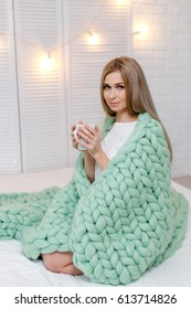 Young pretty blonde woman wrapped in light green merino wool blanket sitting on bed and holding cup of tea. Plaid of thick yarn. Chunky knit.