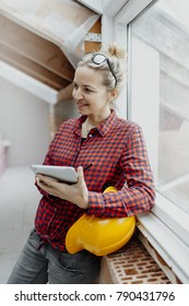 young, pretty, blonde woman with yellow helmet is planning on the notebook and tablet the expansion of her loft