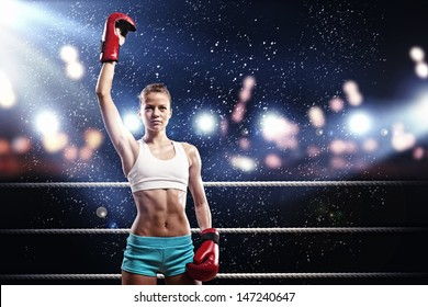 Young pretty boxer woman standing on ring under water drops