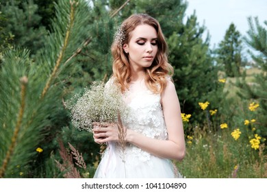 young pretty bride in white wedding dress outdoors, make up and hairstyle