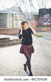 young pretty brown hair caucasian girl listening music with headphones, holding a smartphone in her hand, looking downward, dancing and smiling - music, relaxing, happiness concept