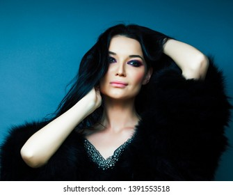 young pretty brunette girl with fashion makeup posing elegant in fur coat with jewelry on blue background, lifestyle people concept
