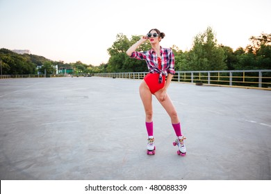 Young pretty brunette girl in sunglasses and red swimsuit posing wearing roller skates on the open road outdoors