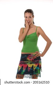 A young pretty brunette wearing a green tank top and colorful summer skirt posing playfully and smiling at the camera. Isolated on white.