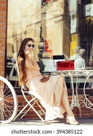 young pretty brunette woman after shopping sitting at cafe outside on street smiling