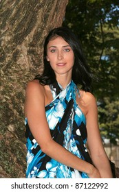 Young pretty brunette woman in a blue,white and black sarong in the shade of a tree.