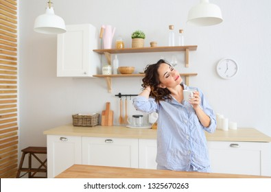 Young pretty brunette woman drinking her morning coffee at kitchen