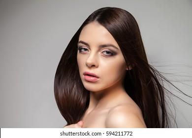 Young pretty brunette woman looking at camera. Horizontal studio shot.