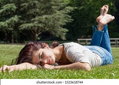 Young pretty brunette woman lying  on grass in a park