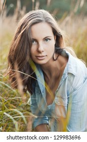 Young pretty brunette woman posing outdoor in summer meadow. Sensual girl posing in park