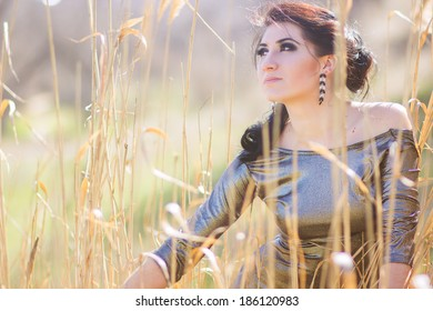 Young pretty brunette woman posing outdoor in summer meadow  Sensual girl posing in park