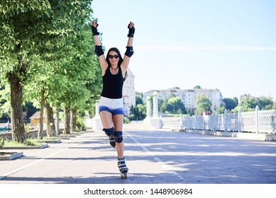 Young pretty brunette woman, riding rollerblades in city park with green trees. Fit sporty girl, wearing black top and white shorts, roller-skating, raising her arms up, showing joy and happiness.