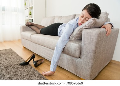 young pretty business woman after work lying down on sofa couch sleeping resting when she working long time and feeling tired.