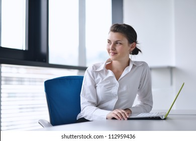 Young pretty business woman with notebook in the bright modern office indoors