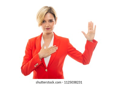 Young pretty business woman showing oath gesture isolated on white background
