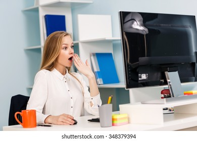 Young pretty business woman sitting at the desk with computer in blue office