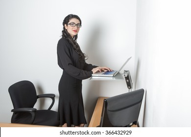 Young pretty business woman standing up using computer in the office looking at camera