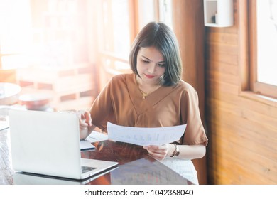 Young pretty business woman working at workplace in office