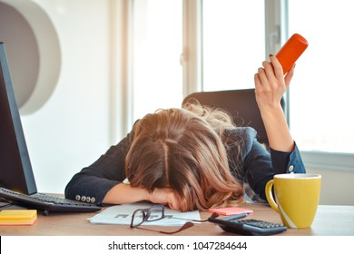 A young pretty businesswoman, exhausted from work sleeping in front of her laptop, leaning on office desk with a telephone handset on hand.