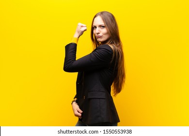 young pretty businesswoman feeling happy, satisfied and powerful, flexing fit and muscular biceps, looking strong after the gym against orange background