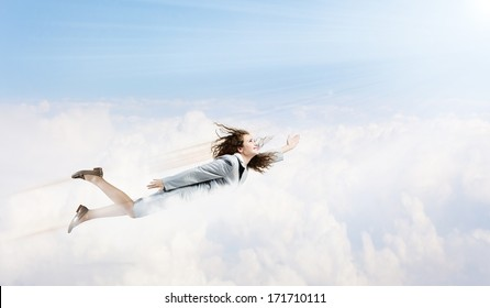 Young pretty businesswoman flying in blue sky