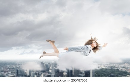 Young pretty businesswoman flying in sky above city