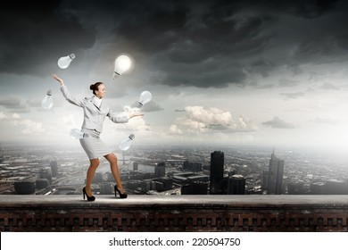 Young pretty businesswoman juggling with light bulbs