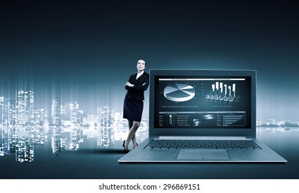 Young pretty businesswoman leaning on big laptop