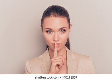 Young pretty businesswoman making silent gesture with finger on lips