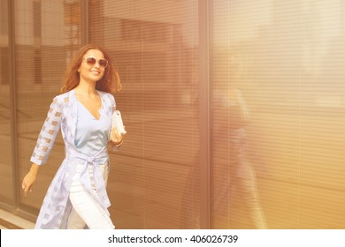 Young pretty businesswoman in sunglasses smiling and walking near business building. She is is a hurry to the meeting with her partners.