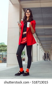 Young pretty businesswoman texting outdoors. Beautiful young stylish asian woman in full lenght in red casual suite and glasses with phone and cup of coffee smiling and looking at camera against