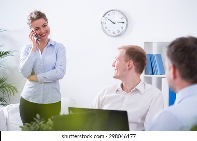 Young pretty businesswoman transacting with client on the phone