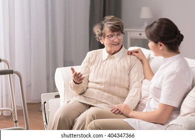 Young pretty caregiver talking with older patient