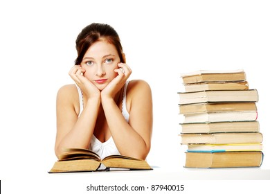 Young pretty caucasian girl holding her head, sitting near the pile of books and thinking.