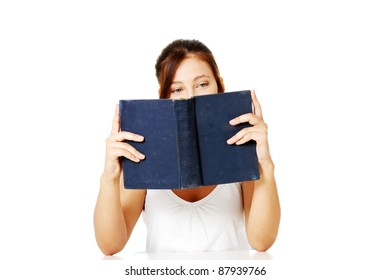 Young pretty caucasian girl reading and hiding behind the book. Isolated on white.