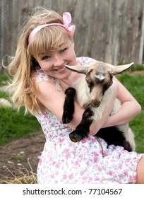 Young pretty cheerful blond woman sitting with goat on a countryside